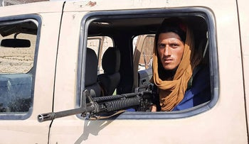 A Taliban fighter sits inside an Afghan military vehicle along the roadside in Laghman province, on Sunday.