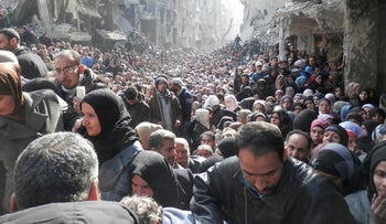 Residents wait to receive food aid distributed by the U.N. Relief and Works Agency (UNRWA) at the besieged al-Yarmouk camp, south of Damascus in 2014.