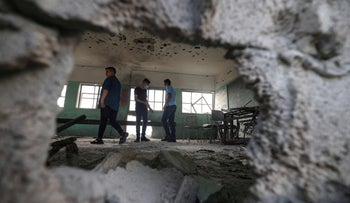 Palestinian students inspect a classroom at a school destroyed during the recent 11-day war between Israel and the Palestinian Hamas movement, in Gaza City, yesterday.