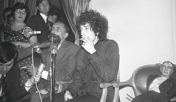 American folk singer Bob Dylan smokes as he faces the media during a press conference at the Hotel George V in Paris, France on May 23, 1966.