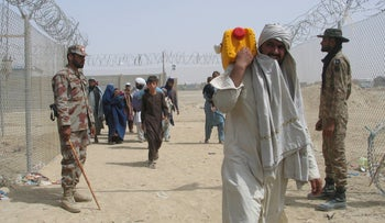 People arriving from Afghanistan make their way to the Friendship Gate crossing point at the Pakistan-Afghanistan border, today.