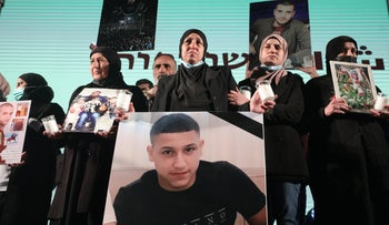 Arab women holding faces of murdered Arabs at a demonstration.