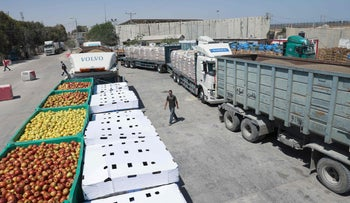 Trucks carrying goods pass through the Kerem Shalom crossing, in late May.