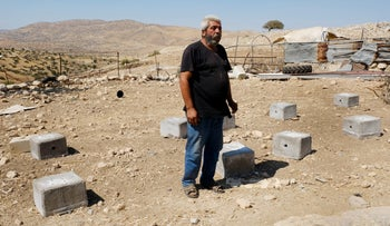 Salim Abu Tayeb and the blocks on which his eight solar panels stood. Two months ago GVC, an Italian NGO, had given the panels to him so his home could have electricity.