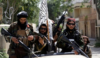Taliban fighters display their flag on patrol in Kabul, Afghanistan on Thursday.