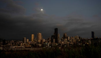The moon over Beirut, as it remains in darkness during a power outage, on Thursday.
