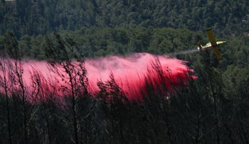 A firefighting plane works to extinguish the flames on Tuesday in the Jerusalem Hills.