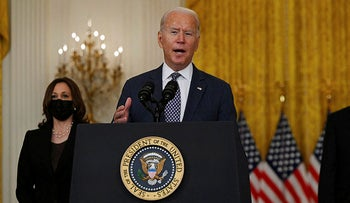 Biden, with Vice President Kamala Harris (L) in the East Room of the White House in Washington, today.