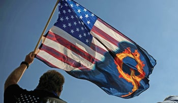 File photo: A Trump supporter holds a U.S. flag with a reference to QAnon during a rally in Oregon, last year.