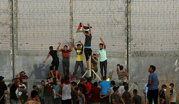 Protestors try to climb the fence of the Gaza Strip's border with Israel, August 21, 2021.