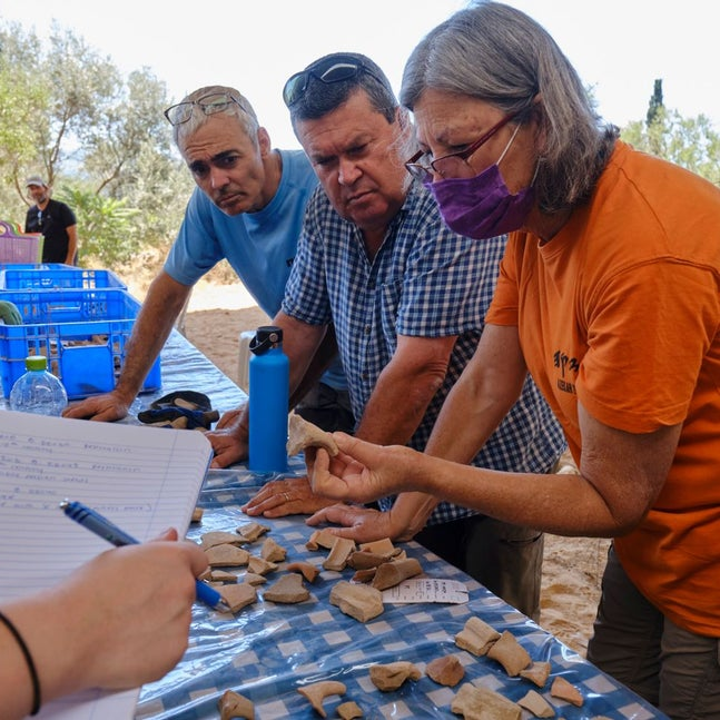 Shua Kisilevitz  (left), Oded Lipschits (middle right) studying fragments found at the site