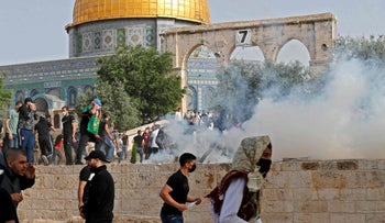 Palestinian protesters run for cover from tear gas fired by Israeli security forces amid clashes at Jerusalem's Al-Aqsa mosque compound in May.