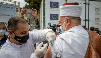 A Palestinian Muslim cleric receives COVID-19 vaccine in the West Bank city of Ramallah