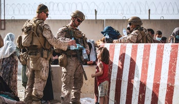 Two U.S. Marines share their water with a young girl at Hamid Karzai International Airport, in Kabul, Afghanistan, on Saturday.