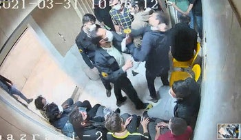 In a frame grab taken from a video shared by the self-identified hacker group called 'The Justice of Ali,' a guard beats a prisoner at Evin prison in Tehran, Iran.