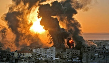 Heavy smoke and fire rise from Al-Sharouk tower as it collapses after being hit by an Israeli air strike, in Gaza City