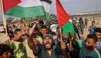 Palestinian protesters lift national flags gesture during a demonstration by the border fence with Israel, Saturday.
