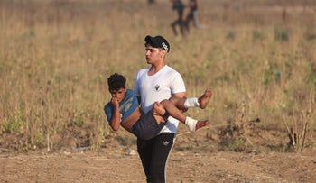A Gazan protester carries an injured youth amid clashes with Israeli security forces during a demonstration near the Israeli border on Saturday.