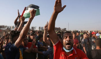 Palestinians shout slogans as they protest along the border fence, east of Khan Yunis in the southern Gaza Strip, yesterday.