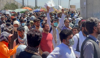 Crowds of people show their documents to U.S. troops outside the airport in Kabul, Afghanistan, on Thursday.