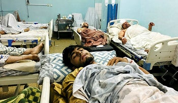 Wounded Afghans lie on a bed at a hospital after a deadly explosions outside the airport in Kabul, Afghanistan, August 26, 2021.