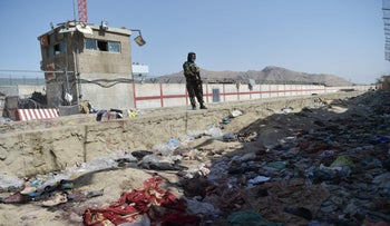 A Taliban fighter stands guard at the site of two powerful explosions, which killed scores of people including 13 U.S. troops on August 26, at Kabul airport on Thursday.