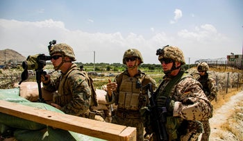 U.S. Marines survey an entry gate at Hamid Karzai International Airport in Kabul, Afghanistan, Saturday, on Saturday.