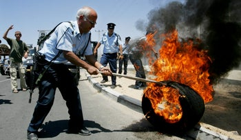 A police officer extinguishing a fire as settlers protest Israel's disengagement from Gaza in 2005.
