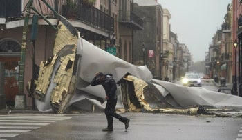 A man passes by a section of roof that was blown off of a building in New Orleans, Sunday.