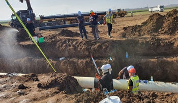 Workers clear contaminated soil near Moshav Mash'en, in southern Israel, on Monday.