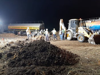 Workers clear contaminated soil near the Moshav Mash'en, in southern Israel, on Sunday night.
