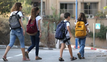 Children escorted by a parent making their way to school in southern Israel as schools reopen across the country, today.