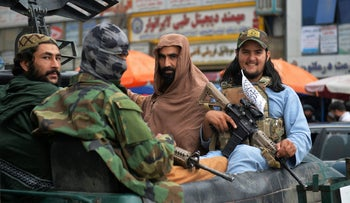 Taliban fighters patrol on a pick-up vehicle along in a street in Kabul, Tuesday.