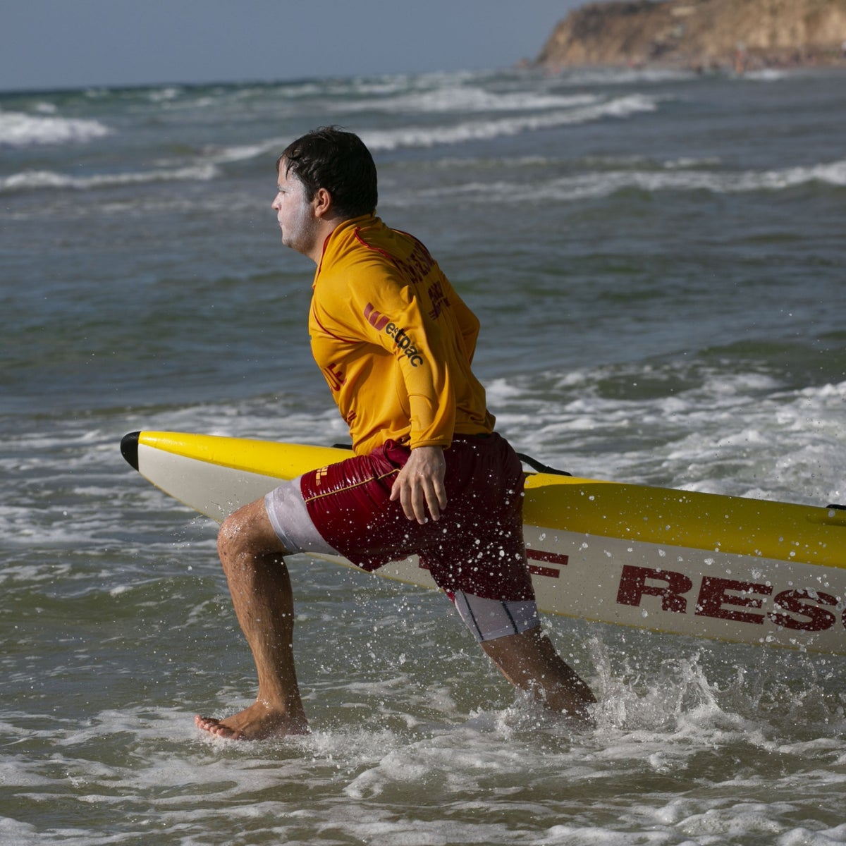 A volunteer at Surf Life Saving course in Herzliya runs into the sea during a practice rescue mission, last month.