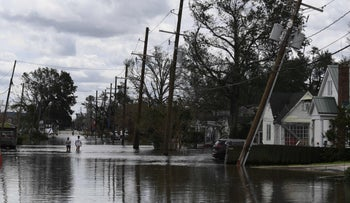 People walk through floodwaters in Norco, Louisiana after Hurricane Ida, on Monday.