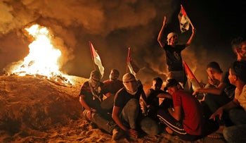 Palestinians gather during a night protest along the border fence with Israel, Thursday.