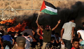A Palestinian demonstrator raises a national flag during a protest along the border fence, last week.