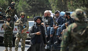 Taliban fighters stand guard along with other fighters on a street in Kabul on August 29, 2021.
