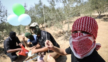 Masked Palestinians launching incendiary balloons from Gaza into Israel, last week.