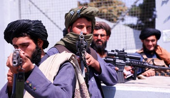 Taliban forces stand guard in front of Hamid Karzai International Airport in Kabul, Afghanistan, this month