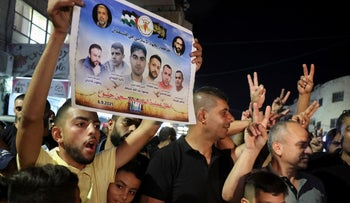 A Palestinian man flashes a poster by the militant group Islamic Jihad of the six Palestinians who escaped from an Israeli prison, as people celebrate in the Jenin camp in the West Bank, on Monday.