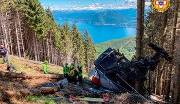 Rescuers work by the wreckage of the cable car after it collapsed near the summit of the Stresa-Mottarone line in the Piedmont region, northern Italy.
