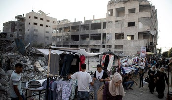 Palestinian street vendors next to the rubble of destroyed buildings after an 11-day war between Hamas and Israel, in Gaza City, in July.