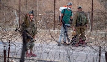 Israeli soldiers by the West Bank security fence, on Wednesday