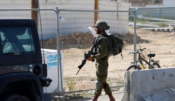 An Israeli soldier stands guard following a reported stabbing attack at the junction of Gush Etzion, near Bethlehem in the West Bank, on Monday.