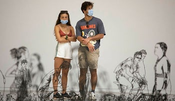 Museum goers wear masks while visiting an exhibition at the Tel Aviv Museum of Art