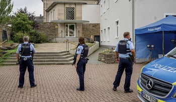 Police officers stay in front of the entrance to the Jewish Community building in Hagen, Germany, today.