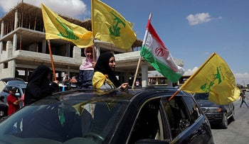 Hezbollah supporters wave Iranian and Hezbollah flags as they celebrate the arrival of Iranian fuel tankers to Lebanon, today.