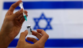An Israeli military paramedic prepares a Pfizer COVID-19 vaccine, to be administered to elderly people at a medical center in Ashdod, southern Israel earlier this year
