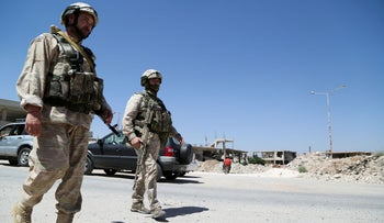 Russian military police members walk near damaged buildings in Deraa, Syria, earlier this month.